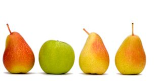 Difference. 3 red pears in a line and one green apple Royalty Free Stock Photos