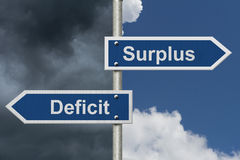 Difference between a Surplus and a Deficit. Two Blue Road Sign with text Surplus and Deficit with bright and stormy sky background Stock Photos