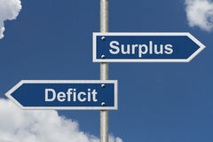 Difference between a Surplus and a Deficit. Two Blue Road Sign with text Surplus and Deficit with sky background royalty free stock images
