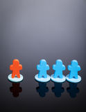Different. One orange and three blue meeples on a dark grey background with room for copy soace above. could be a metaphor for discrimination, different royalty free stock images