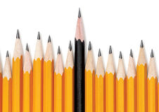 Different. Uneven row of yellow pencils with one black pencil in middle rising taller and standing out from than the rest. On white with drop shadow Stock Image