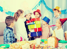 Different ages children giving presents to girl during party. Different ages children giving presents to little girl during party royalty free stock photography