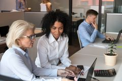 Different ages employees sitting at shared office working together. Middle aged experienced businesswoman company ceo helping to new employee afro millennial royalty free stock photography