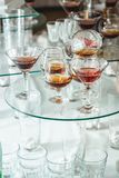 Different alcohol drinks on a glass stand. wine, champagne, cognac, vodka, martini. Different alcohol drinks on a glass stand. wine, champagne, cognac, vodka Stock Photos