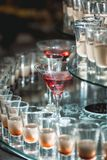 Different alcohol drinks on a glass stand. wine, champagne, cognac, vodka, martini. Different alcohol drinks on a glass stand. wine, champagne, cognac, vodka Royalty Free Stock Images