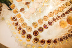 Different alcohol drinks in goblets and wine glasses on wedding buffet table Stock Photos