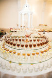Different alcohol drinks in goblets and wine glasses on wedding buffet table Royalty Free Stock Photos