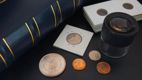 Different American coins on black table with magnifying glass, numismatic supplies and album for coins. Numismatic scene Stock Image