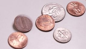 Different American coins rotate and stop in the frame. Close-up. US Small Metal Cash. Movement on a white table. The. Different American coins rotate and stop in stock footage