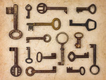 Different antique keys on a retro paper background Stock Photos