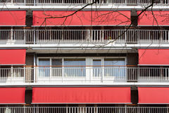 Different. In an apartment block all neighbors use their red awnings against the sunlight. The person living in the middle closes the curtains against the sun Royalty Free Stock Image