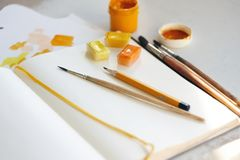 Different art supplies of yellow and orange colors stock photos