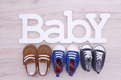 Different baby shoes and word BABY on wooden floor, Royalty Free Stock Photography
