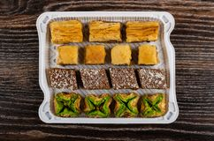 Different baklava in container on wooden table. Top view royalty free stock photography