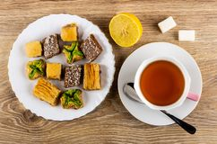 Different baklava in plate, lemon, sugar, cup with tea, spoon on saucer on table. Top view stock photography