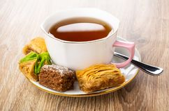 Different baklava, cup with tea, teaspoon on saucer on table royalty free stock photos