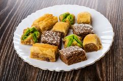 Different baklava in white plate on wooden table royalty free stock photography