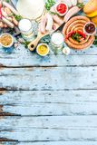 Different bbq picnic party food with beer. Various grilled sausages, burger buns, flat taco bread, beer, old wooden background copy space royalty free stock image