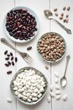 Different bean varieties. White, red and brown beans on plates on a white wooden table. stock photos
