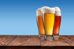 Different beer in glasses on wooden table and blue background Royalty Free Stock Photo