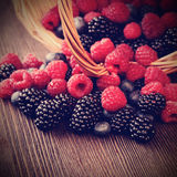 Different berries  in a basket on a wooden table Royalty Free Stock Image
