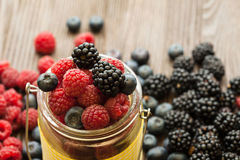 Different berries in a basket on a wooden table Royalty Free Stock Photos