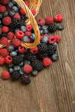 Different berries in a basket on a wooden table Royalty Free Stock Images
