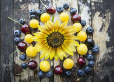 Different berries on a wooden background with sunflower, top view. Fresh different berries on a wooden background with sunflower, top view royalty free stock photos