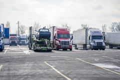 Different big rigs semi trucks with different semi trailers with cargo standing in row on truck stop royalty free stock images