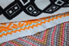 Different black, orange, pink and blue patterns of embroidery on white fabric. Different black, orange, pink and blue patterns of embroidery on a white fabric stock image