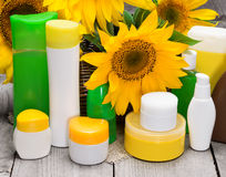 Different body care cosmetics and sunflowers in wicker basket Stock Images