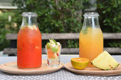 Different bottles of juice with fruits Royalty Free Stock Photos