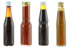 Different bottles of sauce isolated on white. Different bottles of sauce - Oyster sauce, Tomato sauce, Dark soy sauce, Salted soya beans Royalty Free Stock Photography