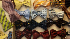 Different bow ties for sale. Photo of many different bow ties neckties of various colors fabric material classic fashion accessory ribbons knots on display for Royalty Free Stock Image
