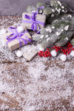 Different boxes with presents, branches fur tree and red berrie. S on textured background. Selective focus.Vertical image. Place for text royalty free stock image