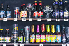 Different brands of Belgian beer bottles and glasses in a liquor Royalty Free Stock Photos