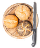 Different bread rolls on cutting board with knife Royalty Free Stock Image
