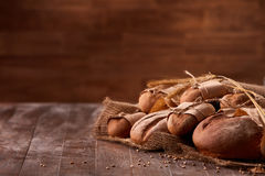 Different bread on the wooden table, paper bags, burlap, rope and ears of wheat with brown blurred background. Royalty Free Stock Photography