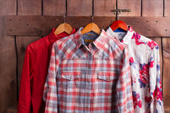 Different bright shirts. Different bright shirts on a wooden fence in a fitting room Royalty Free Stock Photos