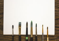 Different brushes are lying on the paper and wooden table Royalty Free Stock Photography