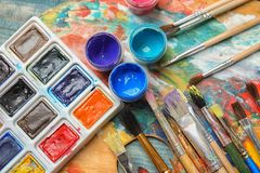 Different brushes and paints on color palette. Top view royalty free stock photo