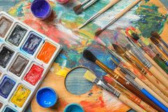 Different brushes and paints on color palette. Top view royalty free stock photography