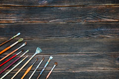 Different brushes to paint on dark wooden background, top view. Concept of art Royalty Free Stock Photos