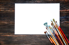 Different brushes to paint on dark wooden background, top view. Stock Photo