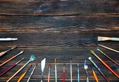 Different brushes to paint on dark wooden background, top view. Concept of art Stock Image