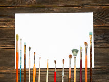 Different brushes to paint with white sheet for records on dark. Wooden background, top view. Concept of art Stock Images