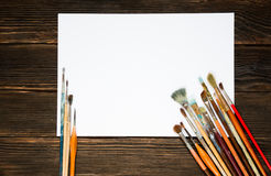 Different brushes to paint with white sheet for records on dark. Wooden background, top view. Concept of art Stock Photos