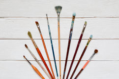 Different brushes to paint on a white wooden background, top vie. W Royalty Free Stock Photography