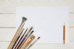 Different brushes to paint on a white wooden background, top vie. W Royalty Free Stock Photo
