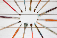 Different brushes to paint on a white wooden background, top vie. W Royalty Free Stock Images